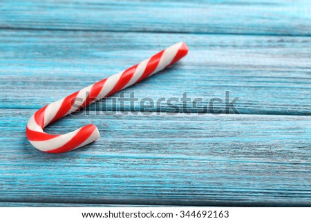 Christmas candy cane on a blue wooden table - stock photo