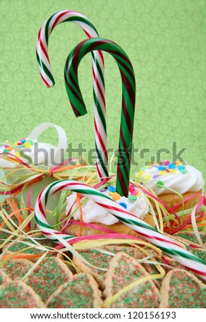 Christmas candy canes with cookies and cupcakes against green - stock photo