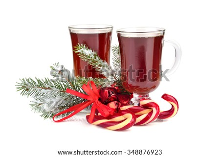 Christmas candy canes with two cups of tea and Christmas green tree twig on white background - stock photo