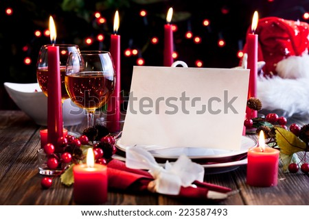 Christmas card in dishware at the wooden table - stock photo