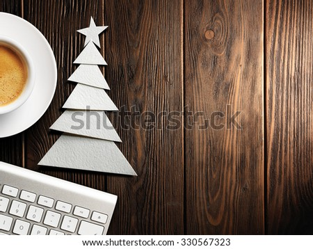 Christmas card. Keyboard, cup of coffee and Christmas tree made of paper on a wooden background - stock photo