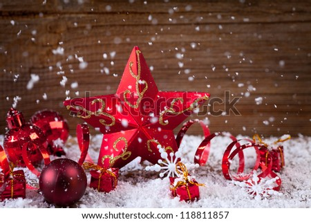christmas card with candle ,baubles,holly and ribbons lying in snow - stock photo