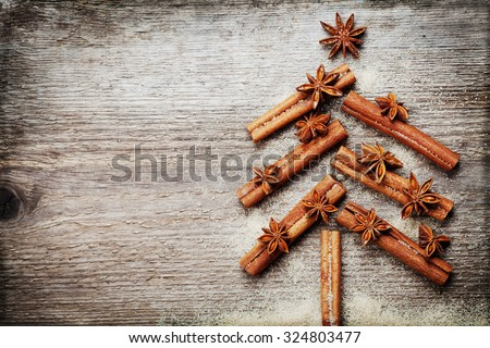 Christmas card with Christmas fir tree made from spices cinnamon sticks, anise star and cane sugar on rustic wooden background, vintage toned, copy space for text, top view - stock photo