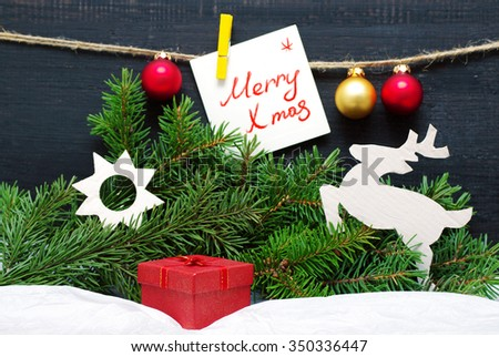 Christmas card with Christmas tree decorations and a fir-tree branch. A card with an inscription Merry X mas and bright Christmas balls on a wooden black background - stock photo