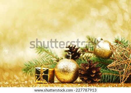 Christmas card with fir branch and decorations on golden gitter background - stock photo