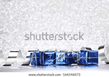 Christmas card with gifts and decoration on shiny silver background - stock photo