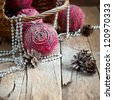Christmas Card with Pink Natural Balls, Pine Cones, Beads on Wooden Background - stock photo