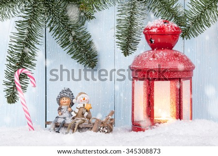 Christmas card with smiling figurines, Christmas lantern and candy canes - stock photo