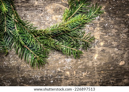 Christmas card with wreath of fir branches on dark wooden background with snow - stock photo