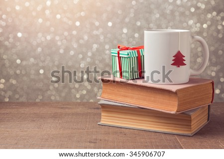 Christmas celebration with cup and gift box on books over bokeh background - stock photo