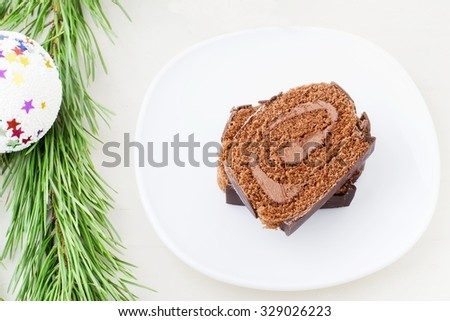 Christmas chocolate roll on a white background - stock photo