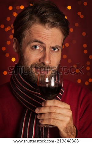 Christmas - close up portrait of forty years old caucasian man tasting or drinking wine. Dark red with lights as background. - stock photo
