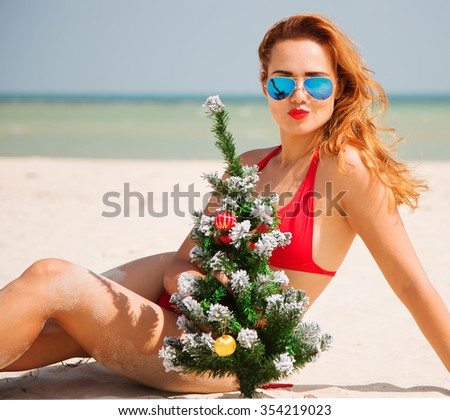 Christmas close up portrait of stunning tanned woman sitting on the beach. Smiling and holding in her hands a Christmas tree. Wearing stylish red bikini and sunglasses. Sporty slim body. Festive mood  - stock photo