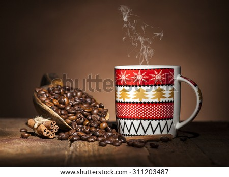 Christmas coffee cup and wooden spoon with coffee beans on wooden and brown background. - stock photo
