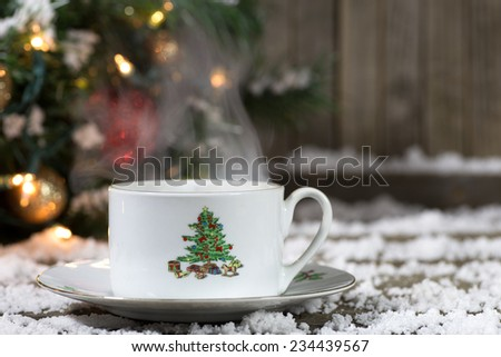Christmas coffee cup on snowy deck with decorations in background - stock photo