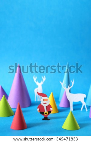 Christmas colorful papercraft scene with santa, deer silhouettes and xmas pine tree shapes, includes copy space. Ideal for holiday greeting card, poster or web. - stock photo