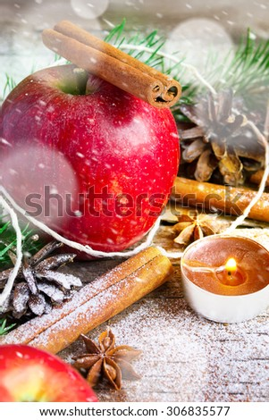 Christmas composition: Apple, candle and cinnamon sticks. Snowing.  - stock photo