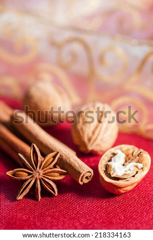 Christmas composition on red fabrics surface. Almonds, cinnamon sticks, star anise, opened walnut and gift ribbon as background. - stock photo