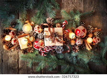 Christmas Composition Top View. Fir Tree Toys with Burning Candles, Boxes, Balls, Pine Cones, Walnuts, Branches of Spruce on Wooden Background - stock photo