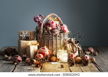 Christmas Composition with Gifts and Burning Candle. Basket, red balls, pine cones, snowflakes on Grey Background. Vintage style - stock photo