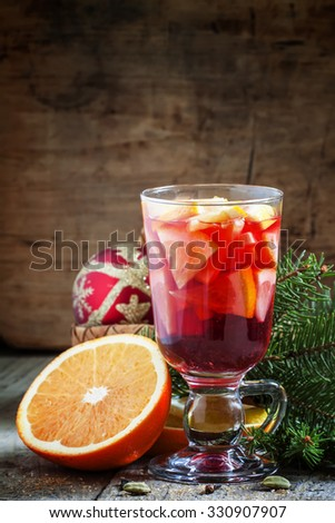 Christmas composition with mulled wine with orange, fir branches and Christmas balls on the old wooden background, selective focus - stock photo