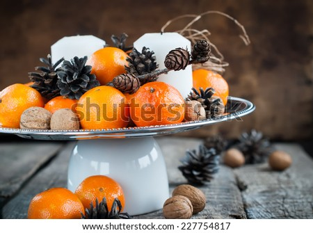 Christmas Composition with Tangerines, Pine cones, Walnuts and Candles on Wooden Background, holiday decoration, horizontal - stock photo
