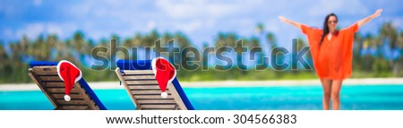 Christmas concept: beach loungers with red Santa Hats and beautiful girl during tropical vacation - stock photo