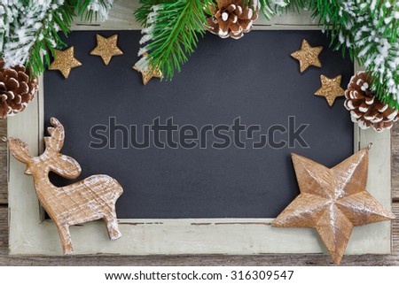 Christmas concept. Black board for text and wooden ornaments, close-up, top view - stock photo