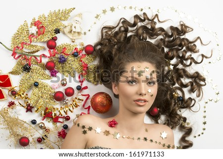 christmas concept close-up portrait of cute curly brunette woman surrounded by colorful xmas decorations, red baubles, golden branch, ribbon and stars on her face.  - stock photo