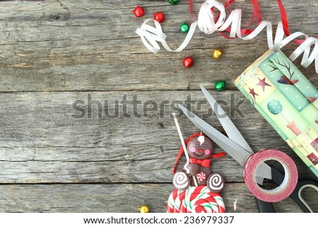 Christmas concept. Material to wrap a gift on wooden board. Use you own text. - stock photo