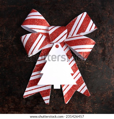 Christmas concept. Red and white bow with blank tag on brown rustic background. - stock photo