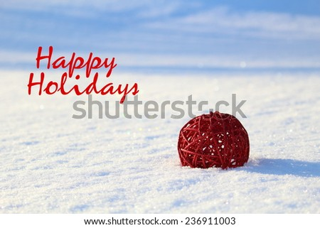 Christmas concept.Red Christmas ball in the snow with the phrase Happy holidays - stock photo