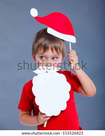 Christmas concept. Smiling funny boy in Santa red hat in studio. - stock photo