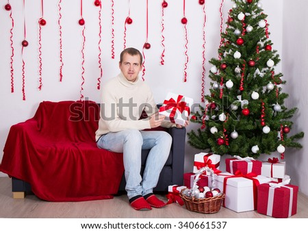 Christmas concept - young man sitting in decorated living room - stock photo