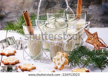 Christmas cookies assorted and glasses of milk cocktail, served with christmas tree branch on wooden table.  - stock photo
