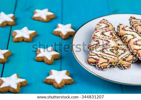 Christmas cookies in a shapes of stars and christmas trees on wooden background - stock photo