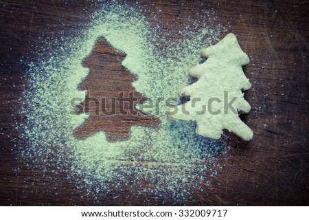 Christmas cookies with cream and powdered sugar on a dark wooden background - stock photo