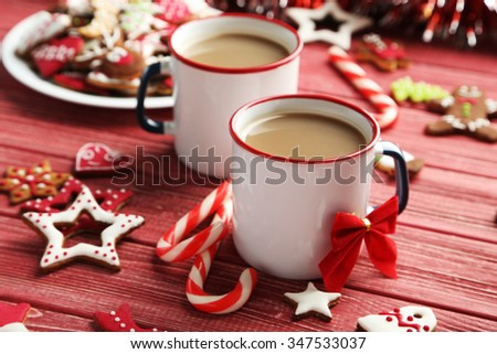 Christmas cookies with cup of hot coffee on a red wooden table - stock photo
