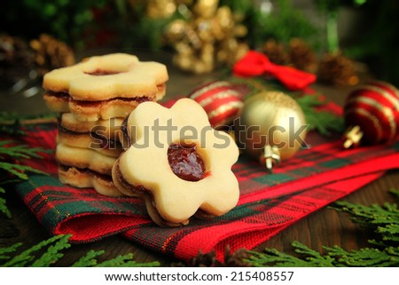 Christmas cookies with flowers shape on a wooden table with christmas balls and cedar branch - stock photo