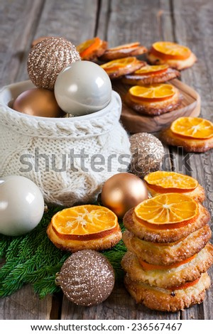 Christmas cookies with sliced tangerine and christmas decoration balls in cup. Selective focus. - stock photo