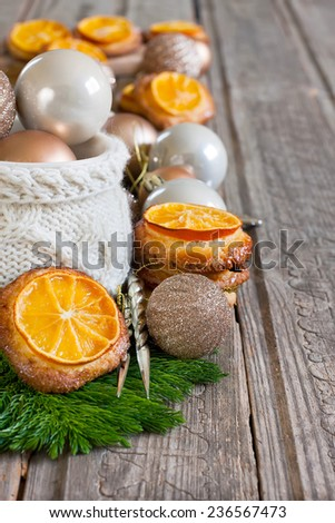Christmas cookies with sliced tangerine and christmas decoration balls in cup. Selective focus. Copyspace background. - stock photo