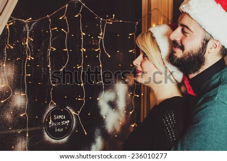 Christmas Couple.Happy Smiling Family at home celebrating.New Year People. Looking trough window. - stock photo