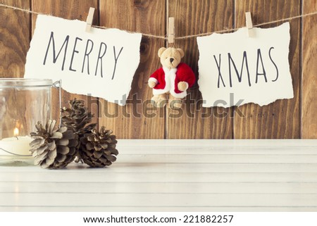 "Christmas cozy scene: a candle and some pinecones on a white wooden table. ""Merry xmas"" and a Teddy bear with Santa Claus dress is hanging on a rope with clothespins. Vintage Style. - stock photo"