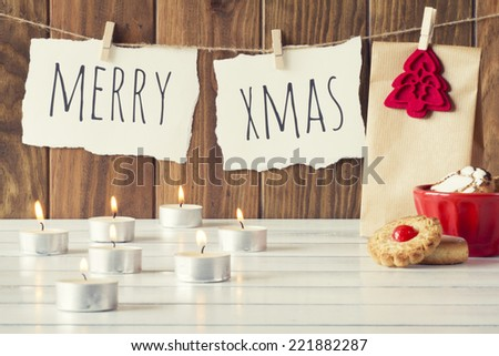 "Christmas cozy scene: some candles, a gift and a red bowl with shortbreads on a white wooden table. ""Merry xmas"" is hanging on a rope with clothespins. Vintage Style. - stock photo"