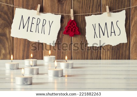 "Christmas cozy scene: some candles on a white wooden table. ""Merry xmas"" and a felt tree is hanging on a rope with clothespins. Vintage Style. - stock photo"