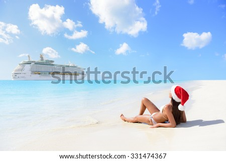 Christmas cruise travel holidays in the Caribbean islands. Woman on new year vacation lying down on beach tanning and relaxing in bikini under the tropical sun. - stock photo