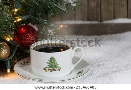 Christmas cup of coffee on snow with decorations in background - stock photo