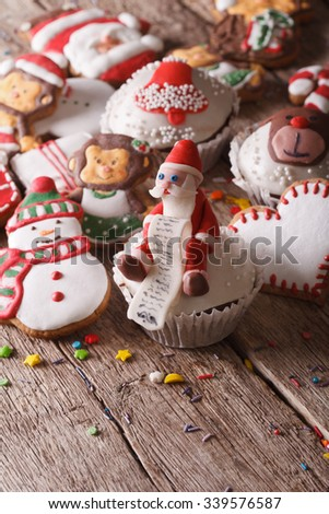 Christmas cupcakes and gingerbread cookies close-up on a wooden table. vertical - stock photo