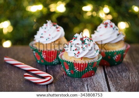 Christmas cupcakes with red and green sprinkles on rustic table. Shallow depth of field. Sparkling Christmas tree lights background.  - stock photo