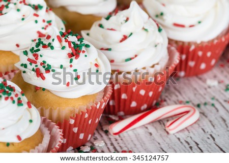 Christmas cupcakes with vanilla frosting and red and green sprinkles on wooden table with a candy cane. Shallow depth of field. - stock photo